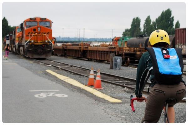 A bike rider on a multi-use path passes by a train yard