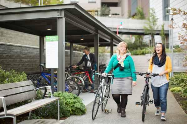 Two women walking their bikes
