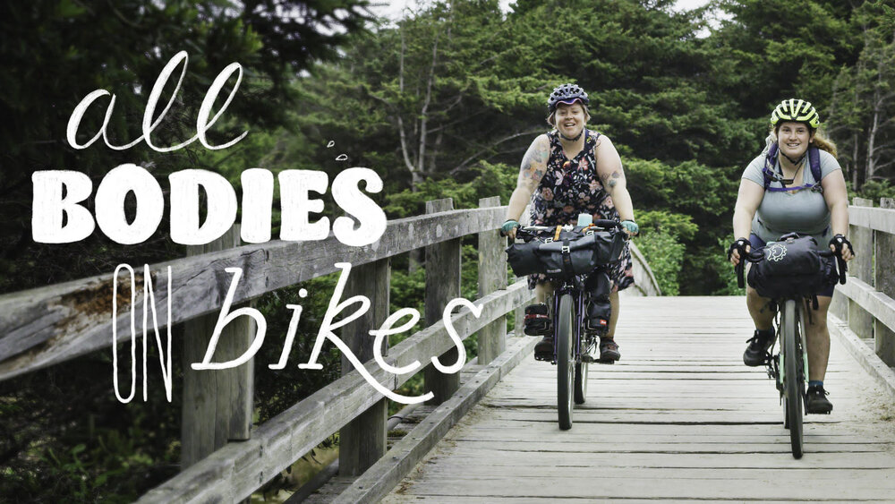 Marley Blonsky & Kailey Kornhauser, featured in the Shimano film All Bodies on Bikes, self-identify as fat cyclists.  Smiling the two ride bikes towards the viewer, on a wooden bridge.