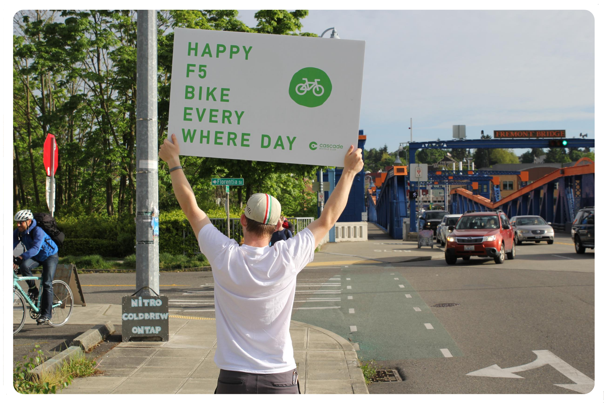 A person holds a sign for Bike Everywhere Day near the blue and orange Fremont Bridge in Seattle.