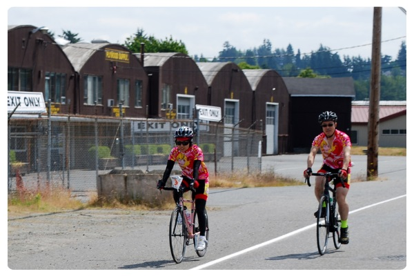 Two people on bicycles ride along the wide shoulder through an industrial area