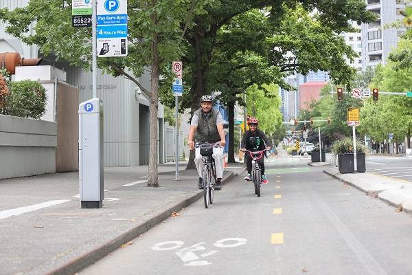 A Black adult male bicyclist and his nephew bike along the 2nd Ave protected bike lane