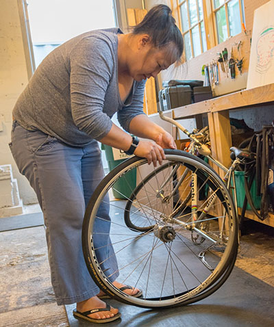 Deborah works her tube and tire back on to her bike wheel