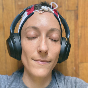 A close up of an olive skinned queer woman, with short dark hair covered in a red, white, and blue (but not particularly American-ish) hat. Eyes blissfully closed, a slight smirk, large noise cancelling headphones cover her ears. She is laying on a wooden