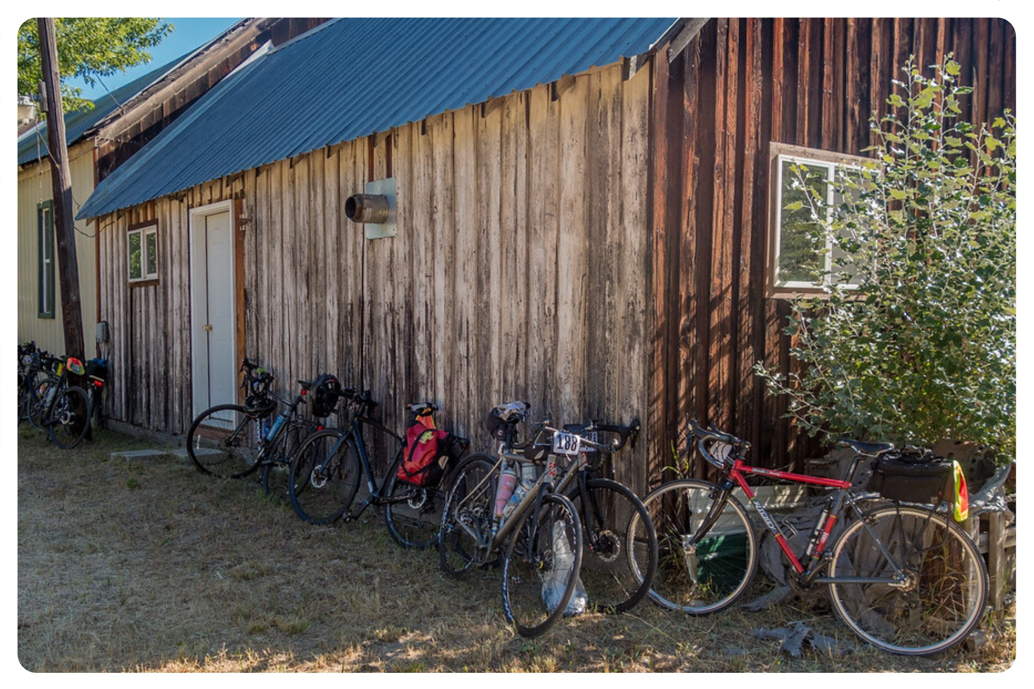 Several bicycles lean against a worn wood-sided building during RAW