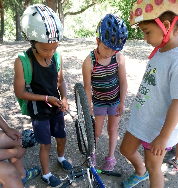 Three kids work together on fixing a bike wheel