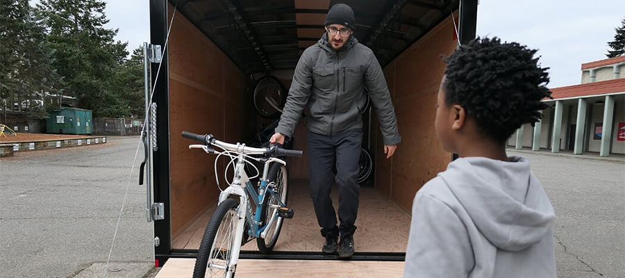 Stephen Rowley, fleet manager, delivers a bike to a child