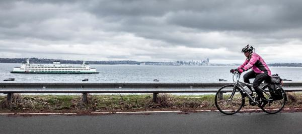 A woman rides past the Puget Sound on Chilly Hilly