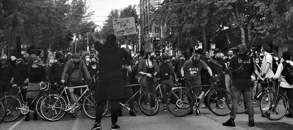 Bikes lined up in front of people protesting the police