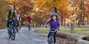 Woman and young girl biking on a trail in the fall