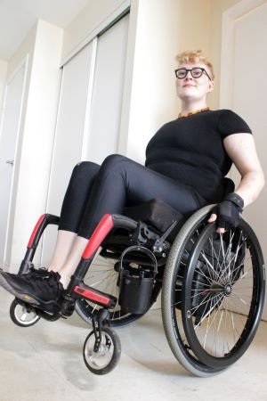 Alex, a white nonbinary person with pale skin and blond hair worn in a messy quiff, pops a wheelie in their red and black lightweight manual wheelchair, while smiling slightly at the camera. Alex is wearing black compression gear, black weightlifting glov