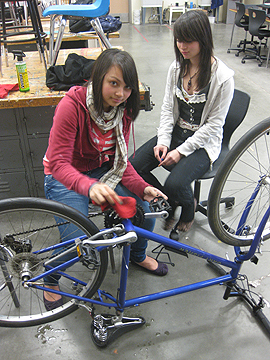 Pricilla and Melissa, putting some elbow grease into a drive train.